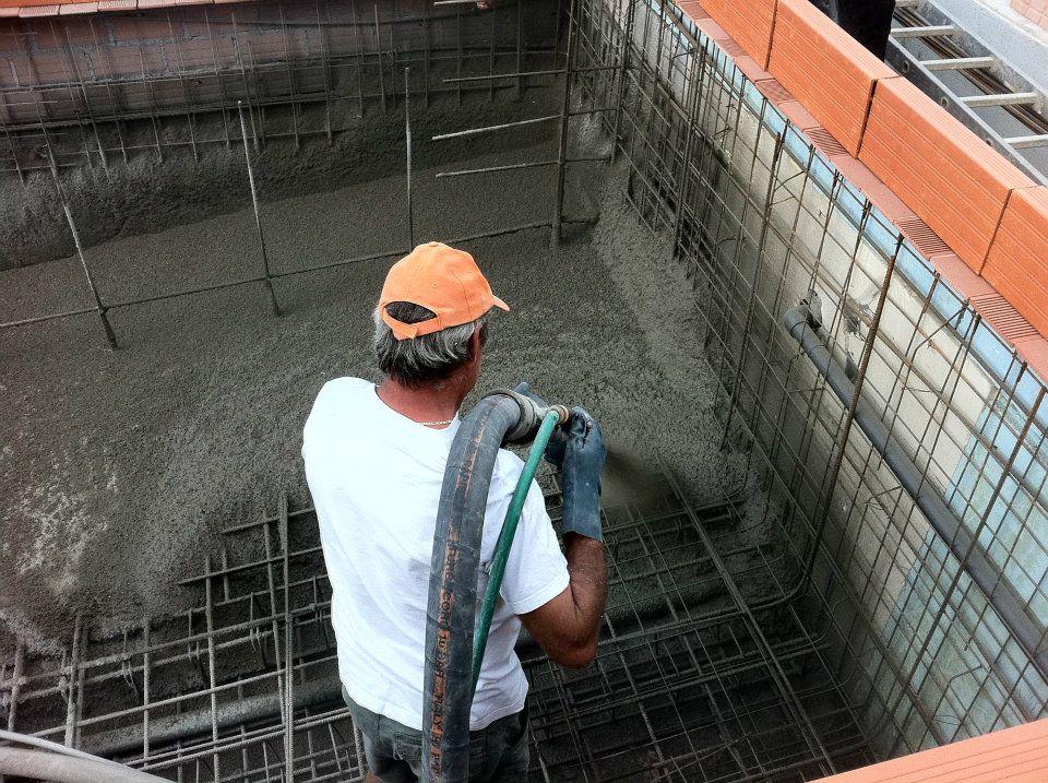 Operario aplicando hormigón en la construcción de piscina de obra